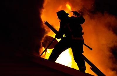 A firefighter silhouetted by fire