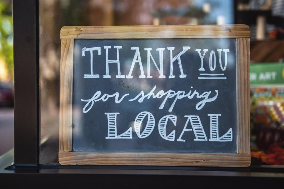 Chalkboard sign in window reading thank you for shopping local